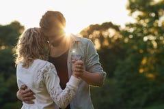 一起跳舞外面在日落的年轻夫妇 免版税库存照片