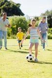 一起踢橄榄球的家庭在公园 库存图片