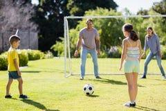 一起踢橄榄球的家庭在公园 图库摄影