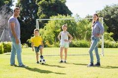 一起踢橄榄球的家庭在公园 免版税库存照片
