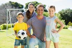 一起踢橄榄球的家庭在公园 库存照片