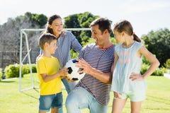 一起踢橄榄球的家庭在公园 免版税图库摄影
