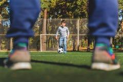 一起踢橄榄球的快乐的家庭 免版税库存图片