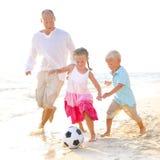 一起踢橄榄球的父亲和他的孩子 库存照片