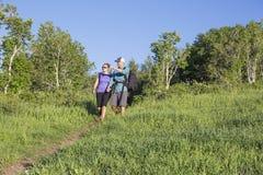 一起远足在山行迹的夫妇 库存照片