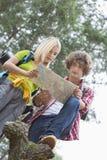 一起远足夫妇读书地图低角度视图在森林里 免版税库存图片