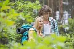 一起远足夫妇读书地图在森林里 免版税库存照片