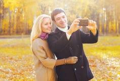 一起采取在smarphone的愉快的微笑的年轻夫妇图片自画象在晴朗的秋天 免版税库存照片