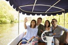 一起采取Selfie的朋友在河的小船乘驾期间 库存照片