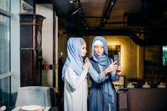 一起采取selfie的激动的年轻回教女朋友 免版税库存图片