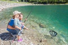 一起钓鱼一条鳟鱼的爸爸和女儿在山湖 库存图片