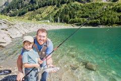 一起钓鱼一条鳟鱼的爸爸和女儿在山湖 库存照片