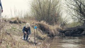 一起钓鱼在河的父亲和儿子 有钓鱼竿的小男孩在岸 股票录像