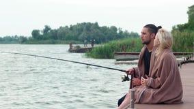 一起钓鱼在湖的恋人清早,人与标尺坐船坞,在船坞的爱夫妇 股票视频