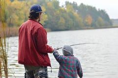 一起钓鱼在秋天天backgound的父亲和小儿子 免版税图库摄影