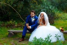 一起钓鱼-浪漫婚礼概念的新娘和新郎 免版税库存图片
