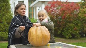 一起雕刻南瓜起重器o灯笼的母亲和女儿,获得乐趣,周末 股票视频