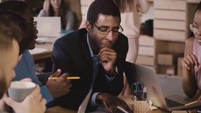 一起非裔美国人的雇员突发的灵感在办公室会议上 由桌的不同种族的商人配合 股票视频