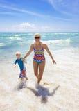 一起飞溅在海滩的家庭 免版税库存图片