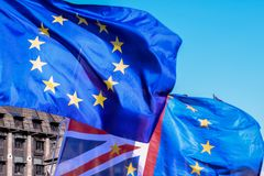 一起飞行在议会之外的欧盟和英国旗子在伦敦 库存图片