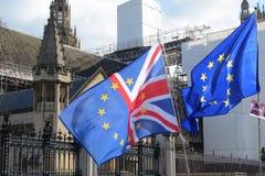一起飞行在议会之外的欧盟和英国旗子在伦敦 免版税图库摄影
