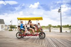一起骑一辆双重萨里自行车的年轻家庭在木板走道 库存照片