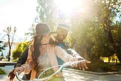 一起骑一辆自行车的可爱的多文化夫妇在晴朗 库存照片