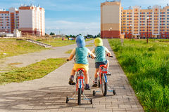 一起骑自行车的两双胞胎 免版税库存照片