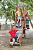 一起滑下来在playground& x27的孩子; s建筑 免版税库存照片