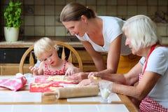一起3个妇女一代烘烤曲奇饼 库存照片
