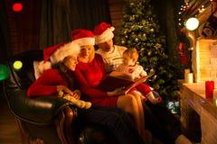 一起读在圣诞节晚上的愉快的四口之家 免版税图库摄影