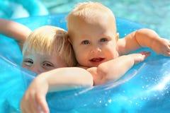 一起婴孩和哥哥在游泳池的木筏 免版税图库摄影