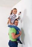 一起绘屋子的父亲和女儿 库存照片