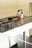 一起读日志的女实业家由玻璃栏杆在办公室 库存照片