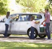 一起洗涤汽车的父亲和女儿 库存照片