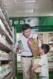 一起购物在超级市场的父亲和儿子,举行袋子和微笑 图库摄影
