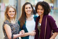 一起购物在购物中心的三个女性朋友 免版税库存图片