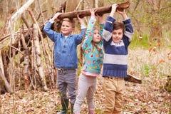 一起建立阵营的孩子在森林 免版税库存照片
