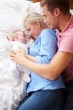 一起说谎与女婴的父母在床上 库存图片