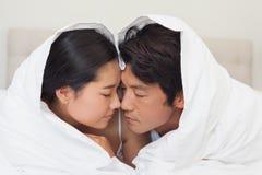 一起说谎在床上的愉快的夫妇在鸭绒垫子下 免版税库存图片