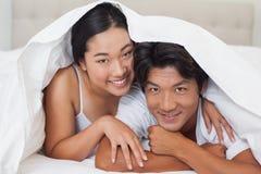 一起说谎在床上的愉快的夫妇在鸭绒垫子下 库存照片