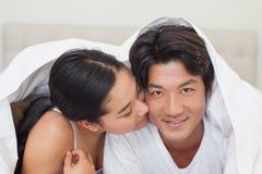 一起说谎在床上的愉快的夫妇在鸭绒垫子下 库存图片
