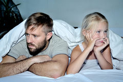 一起说谎在床上的生气的父亲女儿画象  免版税图库摄影