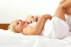 一起说谎在床上的美丽的小女孩 库存照片