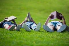 一起说谎在草和阅读书的孩子 库存图片