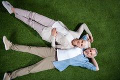 一起说谎在绿草和微笑对照相机的愉快的资深夫妇 免版税库存图片