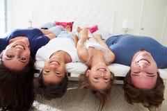 一起说谎颠倒在睡衣的床上的家庭 免版税库存图片