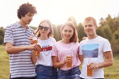 一起Groupmates集会在野餐,庆祝顺利地完成学习年,拿着瓶啤酒或能量饮料,立场nex 库存图片