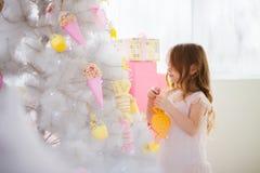 一身庄重装束的小女孩装饰圣诞树 免版税图库摄影