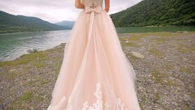 一身庄重装束的红发新娘沿河的河岸走到她的未婚夫 衣物夫妇日愉快的葡萄酒婚礼 股票视频